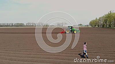Aero Agronomista camina en el campo con filas especiales de tierra Ella prueba, usando tableta, la calidad de la papeleta automat almacen de video