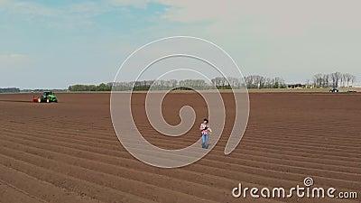 Aero Granjera, agrónomo está en el campo con filas especiales de tierra Ella prueba, usando tableta, la calidad de la automatizac almacen de video