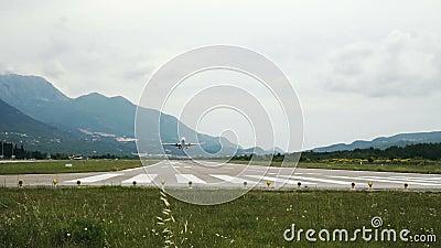 Aeronaves comerciales despegan de la pista con fondo montañoso Montenegro almacen de video