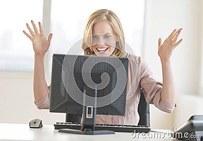 Affärskvinna With Arms Raised som firar framgång, medan se