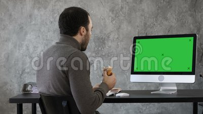 Affärsman i kontoret som har frukosten, lunch och håller ögonen på något på macen, dator Grön skärmmodell lager videofilmer