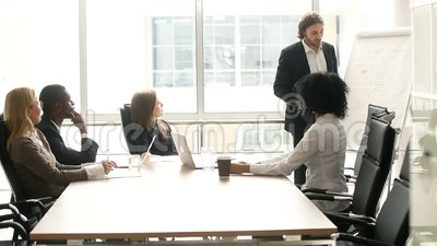 Affärsman som ger presentation till denperson som tillhör en etnisk minoritet klientgruppen på kontorsmötet lager videofilmer