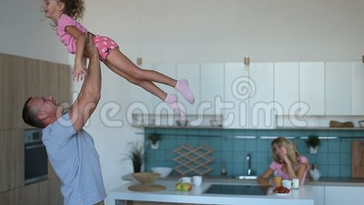 Affectionate dad raising daughter up in the kitchen stock video