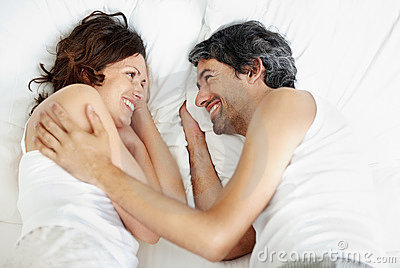 Affectionate middle aged couple lying on bed