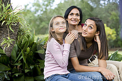 Affectionate mother and two daughters sitting