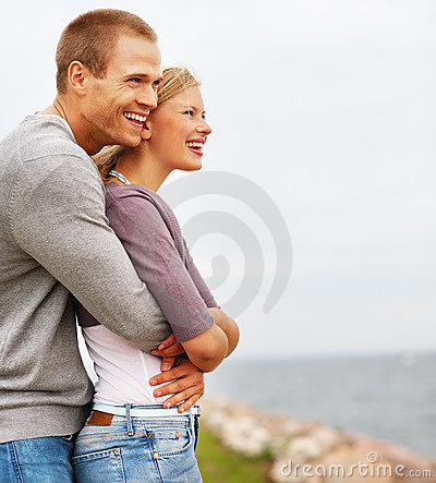 Affectionate young guy embracing his girlfriend