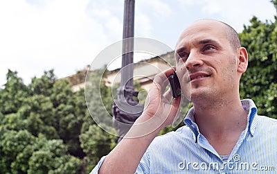 Affärsman som utomhus talar på mobiltelefonen