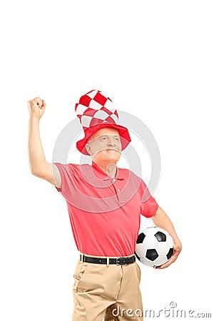 Aficionado deportivo maduro con el sombrero que celebra una bola y gesticular de fútbol