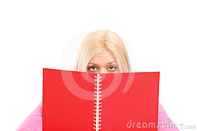 An afraid female covering behind book