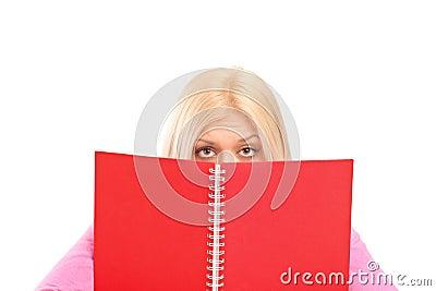 An afraid female covering behind book