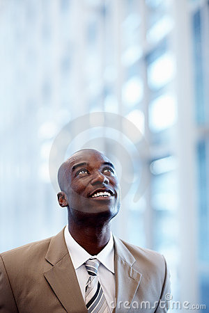 An African American business man looking upwards