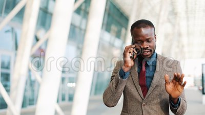 African American businessman walking on street near office center and talking on mobile phone. Business, people. Communication, technology, leisure and stock video footage