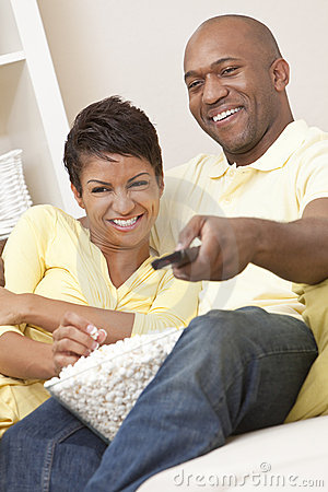 African American Couple Eating Popcorn With Remote