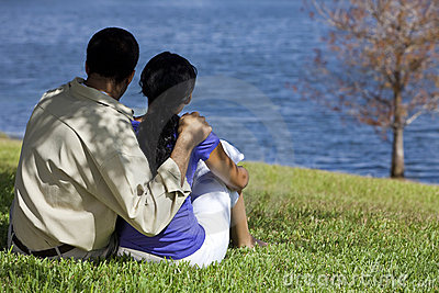 African American Couple Sitting By Lake