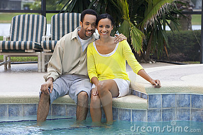 African American Couple Sitting By A Swimming Pool