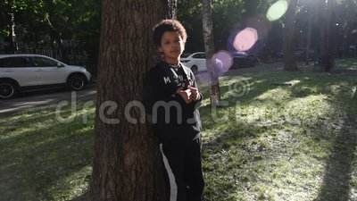 Cool mixed boy walking outside of his house after school stock footage