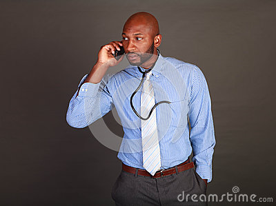 African American Doctor checks his phone