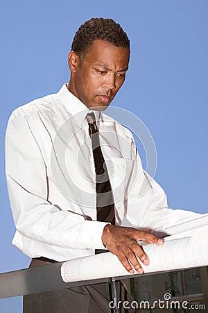African American engineer examining blue print