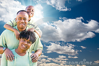 African American Family Over Blue Sky and Clouds