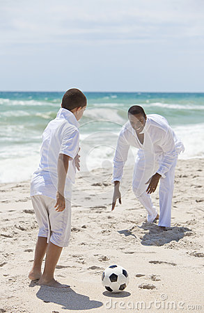 African American Family Playing Football on Beach