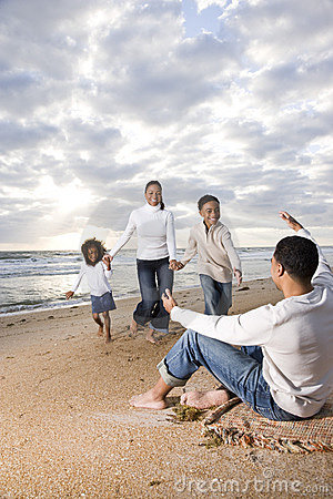 African-American family running to dad on beach