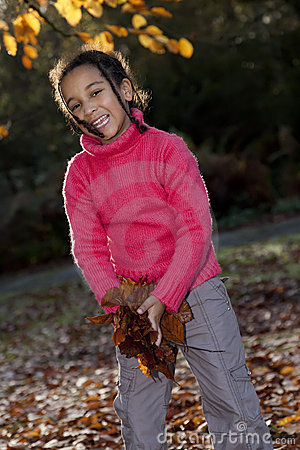 African American Girl Playing With Fall Leaves