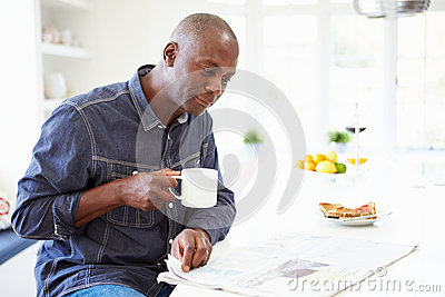 African American Man Eating Breakfast And Reading Newspaper