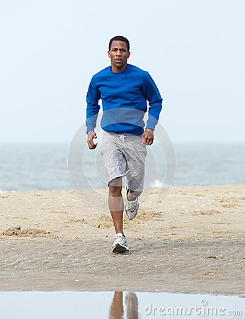 African american man jogging at beach