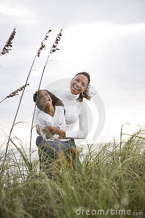 African-American mother daughter laughing at beach