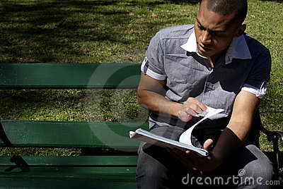 African American Student Reading Outdoors Stock Photo