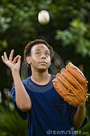 African American teenager tossing a baseball