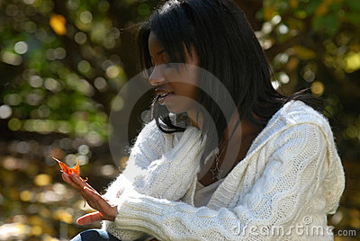 African-American woman gazes at a leaf
