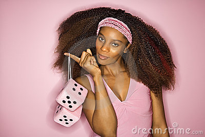 African-American woman holding fuzzy dice.