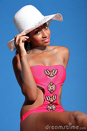 African american woman in monokini and sun hat