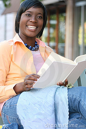 African American Woman Reading a Book Outdoors