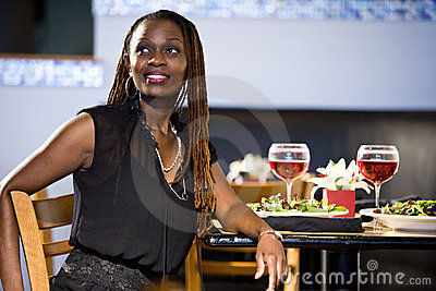 African American woman sitting at restaurant table