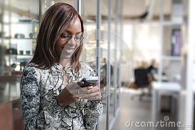 African or black American woman calling or texting on mobile cellphone telephone in office