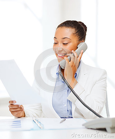 African businesswoman with phone in office