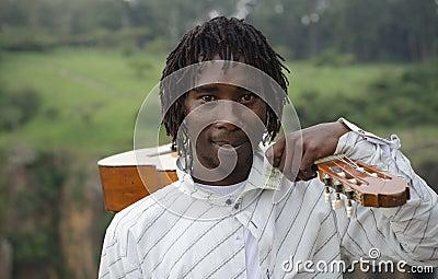 African busker with guitar on shoulder