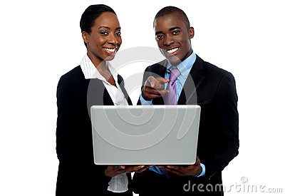 African coworkers operating laptop and pointing