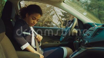 African female driver buckling up seat belt in car. Confident pretty african woman driver in formalwear buckling up seat belt for safety driving in car during stock footage