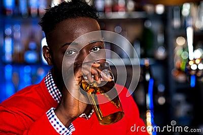 African guy drinking beer, blur background
