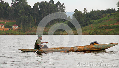 African Man Paddles Dugout Canoe Editorial Image