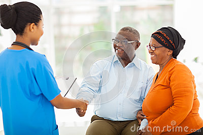 African nurse greeting senior couple