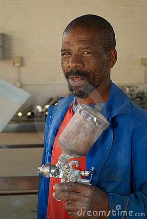 African worker with paint spray gun