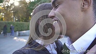 Afrikaans Amerikaans en Kaukasisch meisje die en in het park koesteren kussen stock videobeelden