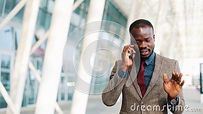 Afrikaanse Amerikaanse zakenman die op straat dichtbij bureaucentrum lopen en op mobiele telefoon spreken Zaken, mensen stock videobeelden