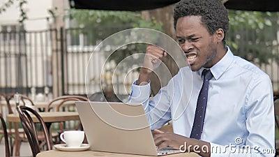 Afrikaanse Zakenman Celebrating op Laptop in Openluchtkoffie stock footage