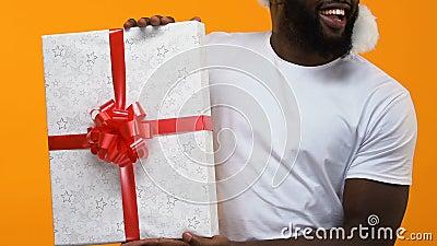 Afrikanisches weißes T-Shirt des jungen Mannes, das große Geschenkbox, Weihnachtsverkauf, Festlichkeit hält stock video footage