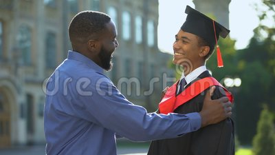 Afro-american father feeling glad graduating son university mantle, achievement. Stock footage stock video